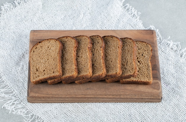 Een houten snijplank met sneetjes bruin brood.