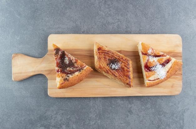 Een houten snijplank met stukjes cake