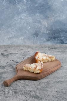 Een houten snijplank met stukjes heerlijke taart op een marmeren tafel.