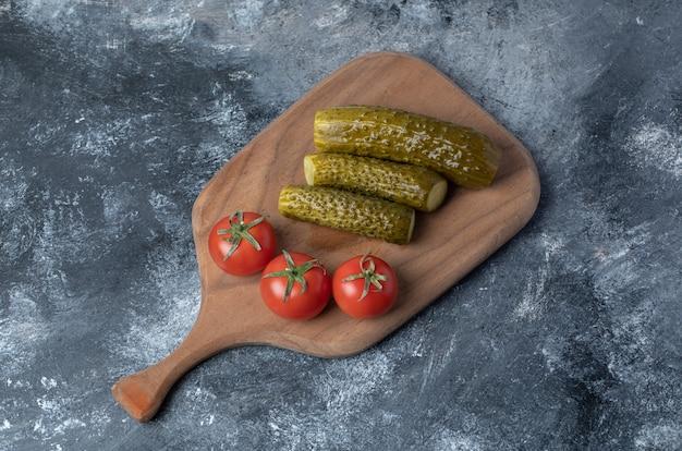 Een houten snijplank van tomaten en ingelegde komkommer.