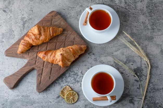 Een houten snijplank van verse croissants en witte kopjes hete thee op een stenen tafel.