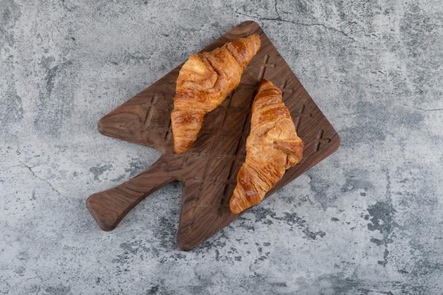 Een houten snijplank van verse croissants op een stenen tafel.