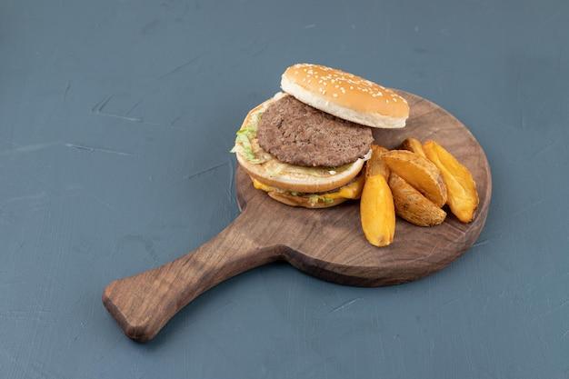 Een houten snijplank vol gebakken aardappelen en hamburger.