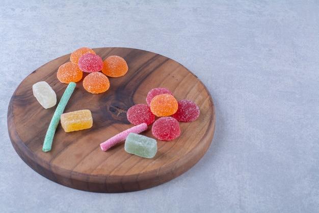 Een houten snijplank vol kleurrijke suikerachtige snoepjes