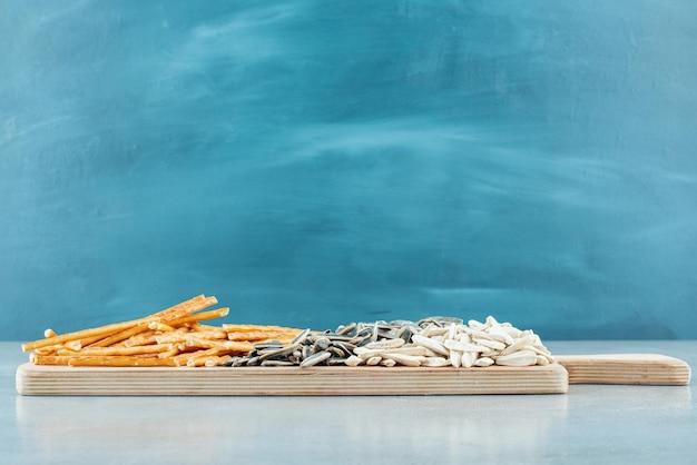 Een houten snijplank vol zonnebloempitten en soepstengels. hoge kwaliteit foto