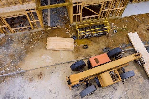 Een houten spant wordt opgetild door een heftruck met hoogwerker in de bouwmaterialen een stapel planken houten frame van een nieuw huis