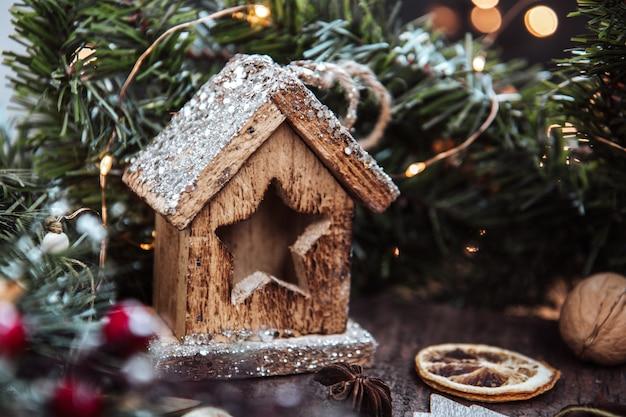 Een houten speelgoed nieuwjaarshuis omgeven door een dennenkrans. kerstmis.