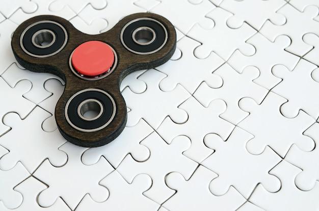 Een houten spinner ligt op een witte puzzelachtergrond