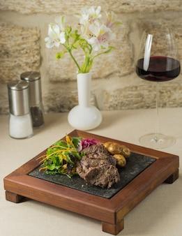 Een houten standaard van biefstuk en aardappelen met groene salade