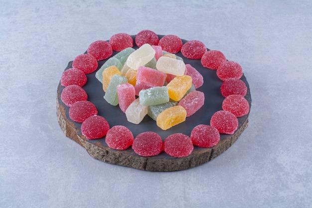 Een houten stuk bord vol kleurrijke suikerachtige gelei-snoepjes