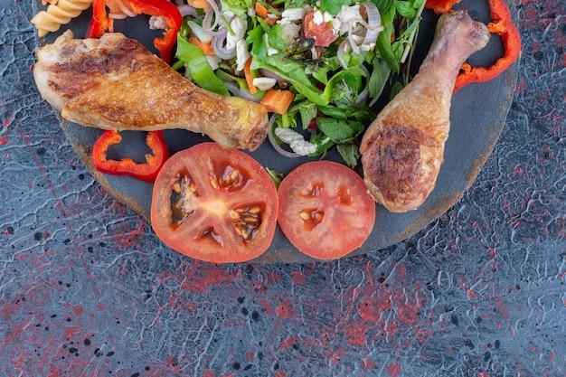 Een houten stuk gebakken kippenpootvlees met groentesalade.