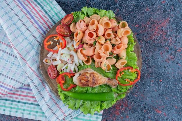 Een houten stuk heerlijk kippenboutvlees met groentesalade