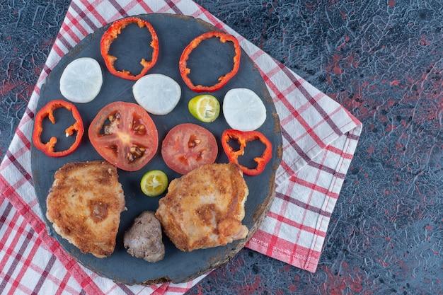 Een houten stuk kip schnitzels met een plakje tomaat.