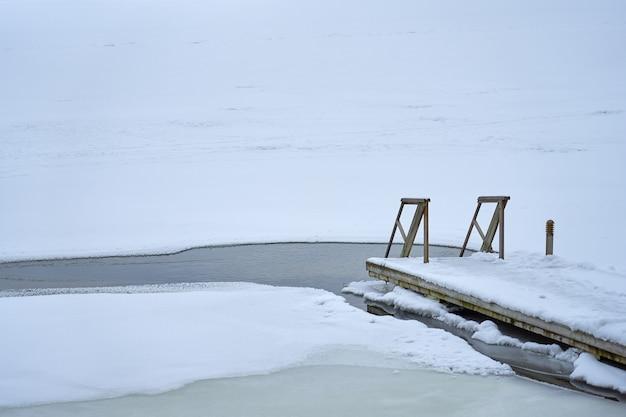 Een houten trap die naar het ijsgat leidt.