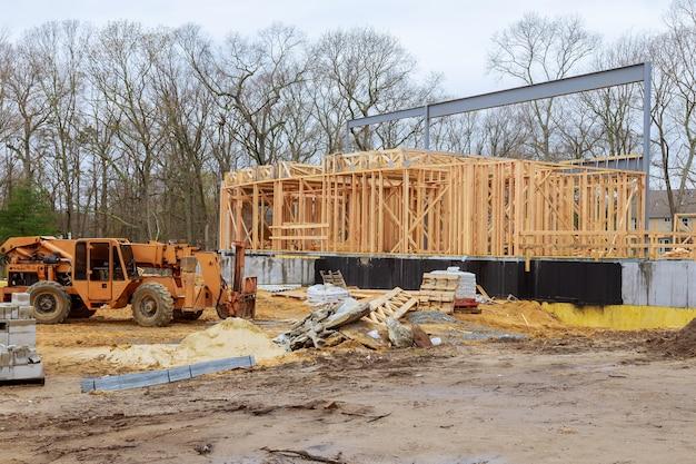 Een houten truss wordt opgetild door een vorkheftruck met giekvrachtwagen in de bouwmaterialen een stapel planken houten frame van een nieuw huis