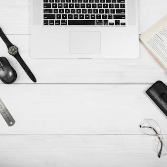 Een houten witte tafel met laptop; muis; bril; boek en polshorloge op wit bureau