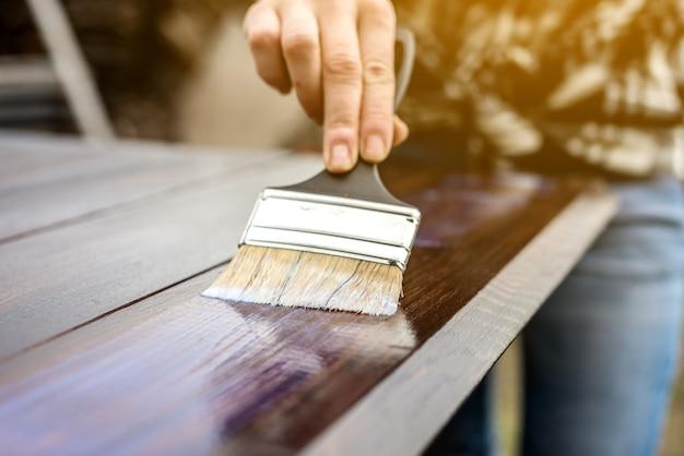 Een houthakker brengt een beschermende laag transparante vernis aan