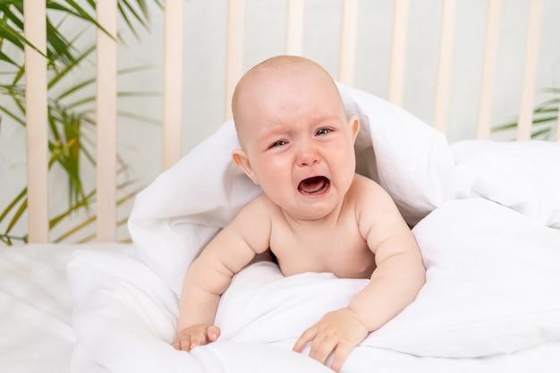 Een huilend babymeisje in een deken in een wieg op een wit katoenen bed van zes maanden is wakker geworden en roept om haar moeder