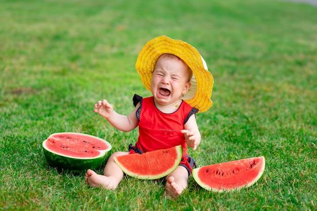 Een huilend kind in de zomer op het groene gras eet een watermeloen, ruimte voor tekst