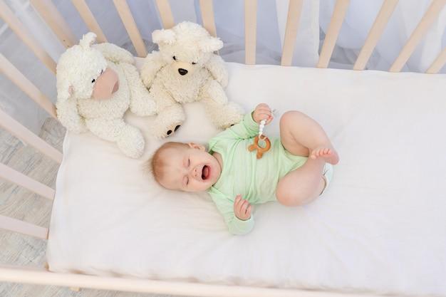 Een huilende baby in een wieg met een bijtring in de slaapkamer