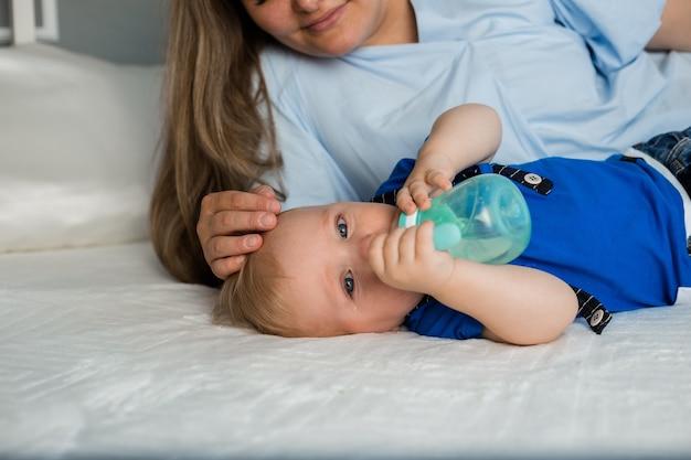 Een huilende baby ligt met zijn moeder op bed en zuigt op een fles