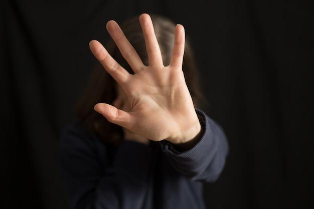 Een huilende vrouw bedekt haar gezicht met haar hand. het huiselijk geweld.