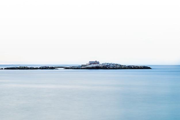 Een huis gebouwd op een klein rotsachtig eiland midden in de zee