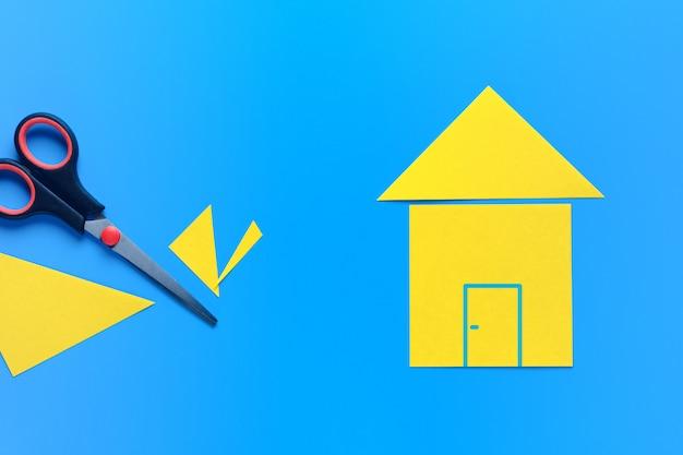 Een huis gesneden uit gekleurd papier op een helder blauw oppervlak. er is een schaar in de buurt.