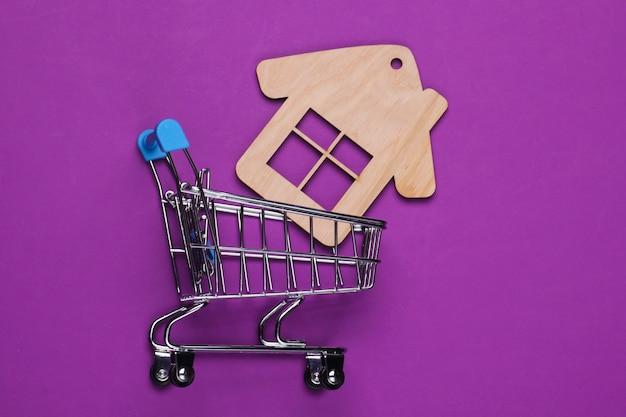 Een huis kopen, miniatuurstilleven. winkelwagentje met huiscijfer op paarse achtergrond.