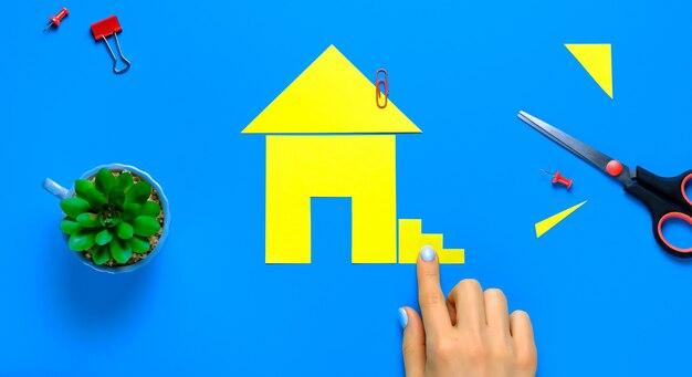 Een huis uit gekleurd papier. de vingers van de vrouw bevestigen de trap. het concept van het realiseren van de droom van uw eigen huis, kopen en bouwen van woningen.