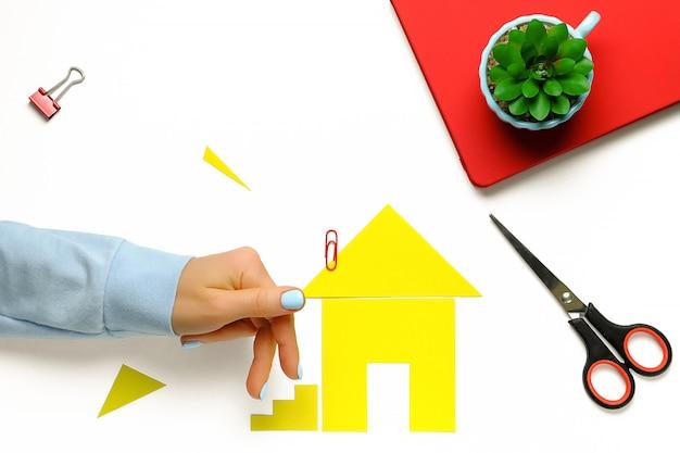 Een huis uit gekleurd papier. de vingers van de vrouw gaan de trap op. het concept van het realiseren van de droom van een huis bezitten, kopen en huizen bouwen.