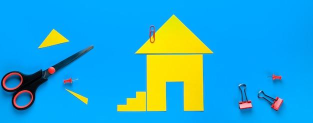 Een huis uit gekleurd papier. er zijn schaar in de buurt. het concept van het realiseren van de droom van een huis bezitten, kopen en een huis bouwen. banier