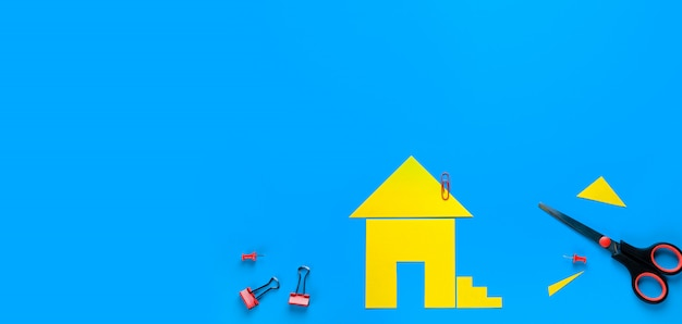Een huis uit gekleurd papier. er zijn schaar in de buurt. het concept van het realiseren van de droom van een huis bezitten, kopen en een huis bouwen. banner.