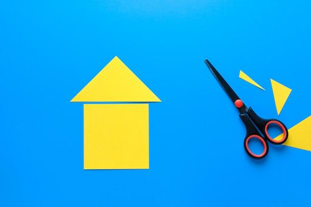Een huis uit gekleurd papier. er zijn schaar in de buurt. het concept van het realiseren van de droom van een huis bezitten, kopen en een huis bouwen.