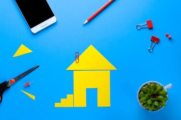 Een huis uit gekleurd papier. ernaast staan een schaar en een mobiele telefoon. het concept van het realiseren van de droom van een huis bezitten, kopen en een huis bouwen.