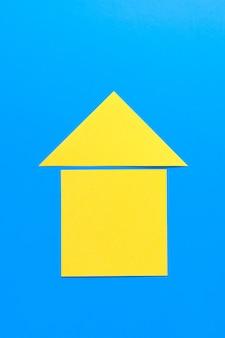 Een huis uit gekleurd papier. het concept van het realiseren van de droom van een huis bezitten, kopen en een huis bouwen.