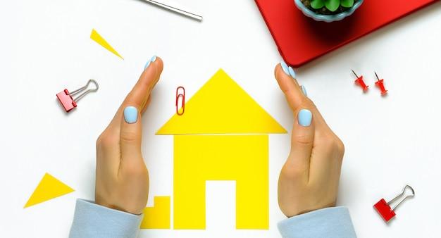 Een huis uit gekleurd papier, tussen de handen van een vrouw. het concept van het realiseren van de droom van een huis bezitten, kopen en een huis bouwen. opslag en amulet van de familie haard en geluk.