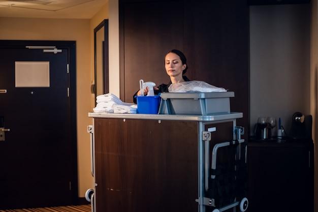 Een huishoudster in een uniform die de kamer schoonmaakt