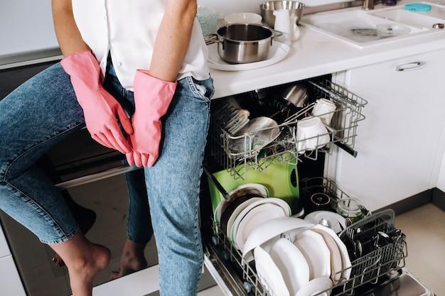 Een huisvrouw meisje in roze handschoenen na het schoonmaken van het huis zit moe in de keuken. in de witte keuken heeft het meisje de afwas gedaan en rust. veel afgewassen vaat.