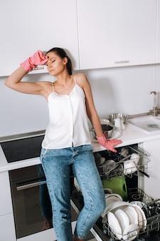 Een huisvrouw meisje in roze handschoenen na het schoonmaken van het huis zit moe in de keuken. in de witte keuken heeft het meisje de afwas gewassen en rust. veel afgewassen vaat.