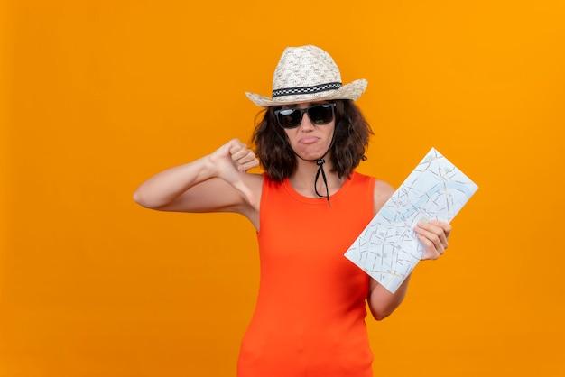 Een hulpeloze jonge vrouw met kort haar in een oranje overhemd met een zonnehoed en een zonnebril met kaart met duimen naar beneden