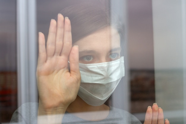 Een humeurige jonge vrouw met een medisch masker achter een glazen raam tijdens de coronaviruspandemie