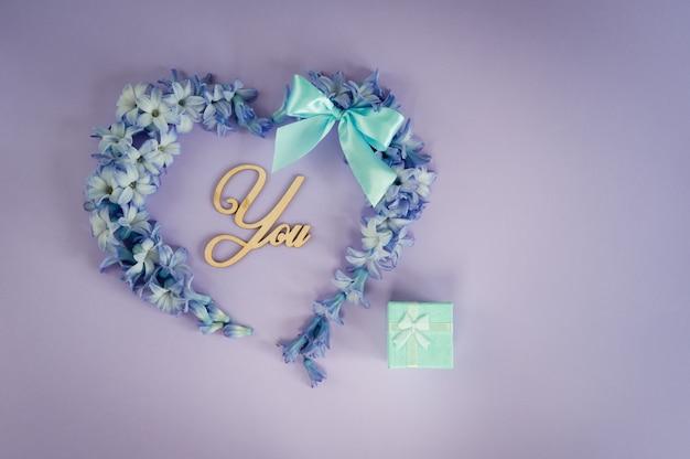 Een huwelijksaanzoek. wil je met me trouwen? hart gemaakt van hyacint bloemen met mint strik