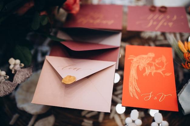 Een huwelijksconcept. uitnodiging en items, verschillende gekleurde papieren enveloppen op tafel
