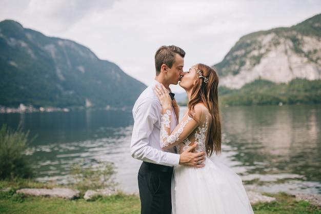Een huwelijkspaar op het achtergrondmeer en de bergen in de sprookjesachtige stad van oostenrijk