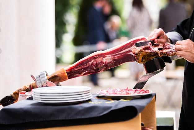 Een iberische hamsnijder die plakjes ham snijdt op een evenement