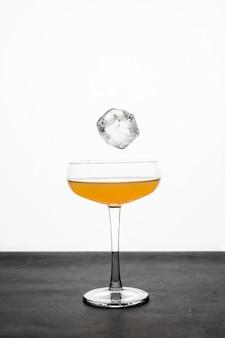 Een ijsblokje dat in een coupeglas valt met een oranje cocktail