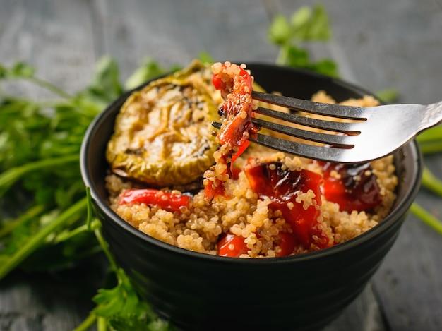 Een ijzeren vork in een zwarte kom met een salade van gekookte quinoa en gebakken groenten. vegetarisch gerecht. natuurlijk plantaardig voedsel. het uitzicht vanaf de top. plat leggen.