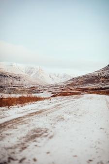 Een ijzige weg in de buurt van bergen in ijsland tijdens de winter
