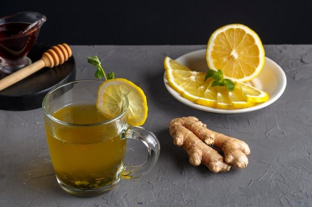 Een immuun gemberdrankje met honing en citroen in een glazen beker naast de ingrediënten. horizontale foto